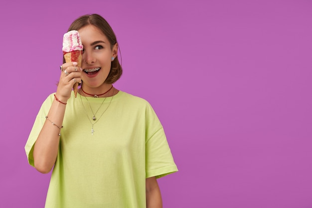 Teenage girl, cheerful and happy, with brunette short hair. holding ice cream over her eye and looking to the right at the copy space over purple wall. wearing green t-shirt, rings and necklace