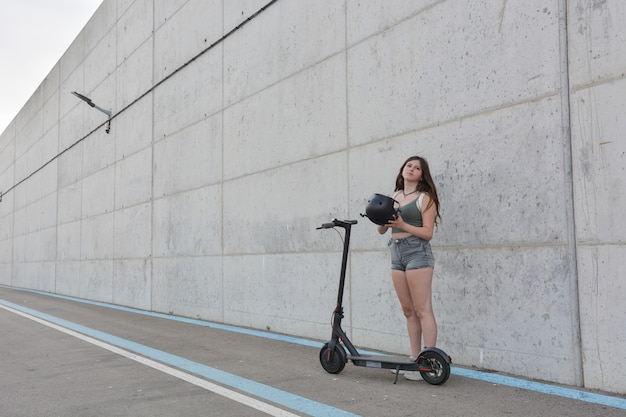 Teenage girl circulating with an electric scooter