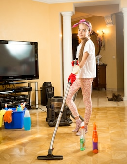 Teenage girl cleaning up floor at room with vacuum cleaner