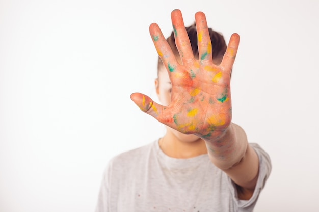 Девочка-подросток закрывает лицо правой ладонью краской