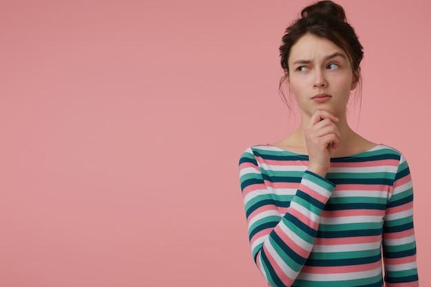 Adolescente, donna dall'aspetto curioso con capelli castani e panino. indossa una camicetta a righe e si tocca il mento, il sopracciglio alzato. guardando a sinistra nello spazio della copia sul muro rosa pastello