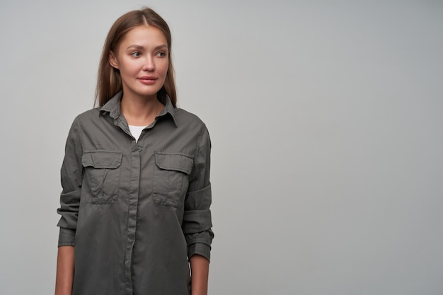 Teenage girl, cute looking woman with brown long hair. looking at something with concentration. wearing grey shirt and watching to the right at copy space, isolated over grey background