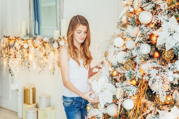 Teenage girl decorating christmas tree on christmas eve at home. young woman in light room with winter decoration. christmas time for celebration concept