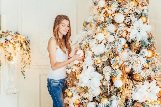 Teenage girl decorating christmas tree o