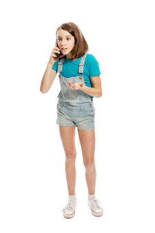 A teenage girl in denim overalls and a blue t-shirt emotionally talks on a smartphone. communication and technology. . full height. vertical.