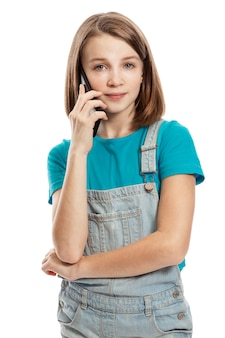 A teenage girl in denim overalls and a blue t-shirt is talking on a smartphone. . vertical.