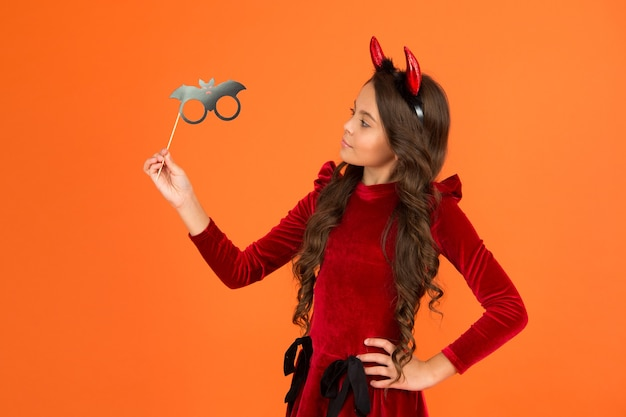 Teenage girl in devil horns celebrate party. halloween sale. happy halloween. trick or treat concept. carnival festive costume of witch. kid with party accessory. child celebrate autumn holiday.