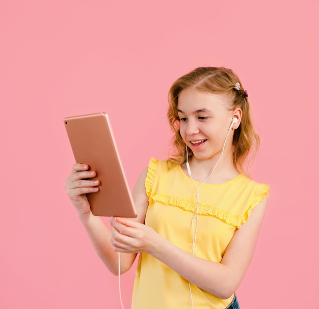 A teenage girl does her homework on a tablet. the student works and communicates with friends.