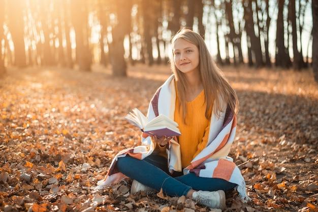 밝은 노란색과 주황색으로 공원에서 책을 읽는 가장 좋아하는 취미를 하는 10대 소녀