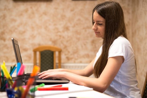 Девочка-подросток делает домашнее задание и просматривает интернет