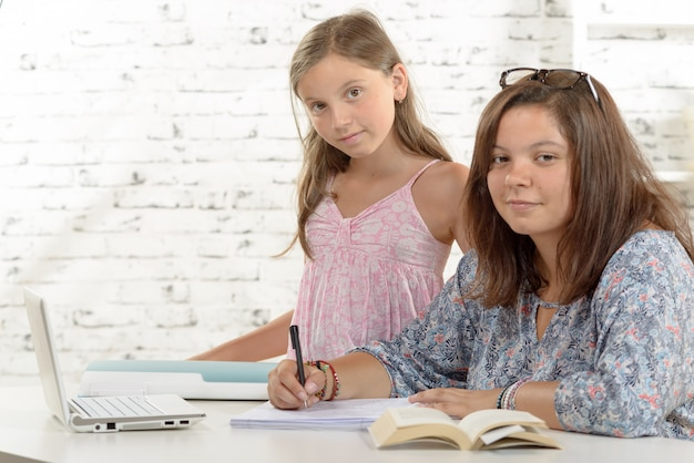 Teenage girl doing her homework with her little sister