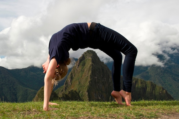 Teenage girl doing wheel pose with valley in the background, the lost city of the incas, machu picchu, cusco region, peru