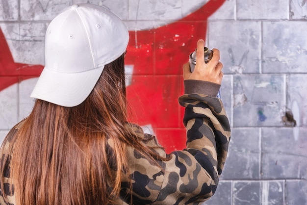 Teenage girl drawing graffiti with spray paint on street wall.