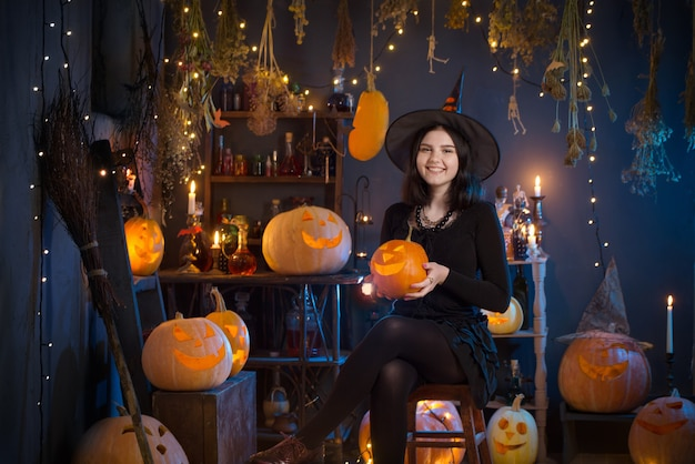 Teenage girl dressed as a witch with pumpkins with decor for halloween