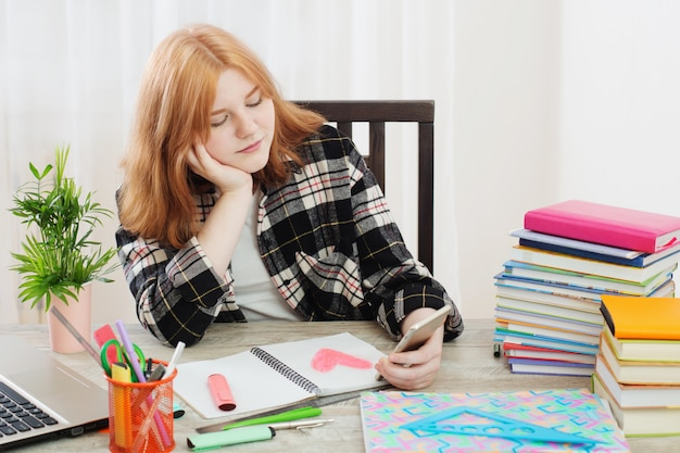 Teenage girl drew a heart in a notebook and looks at the smartphone screen, concept of first love