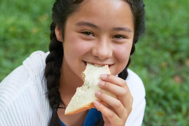 Teenage girl eating sandwich