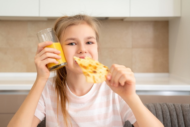 Teenage girl eating a slice of pizza and drinking orange juice in the kitchen