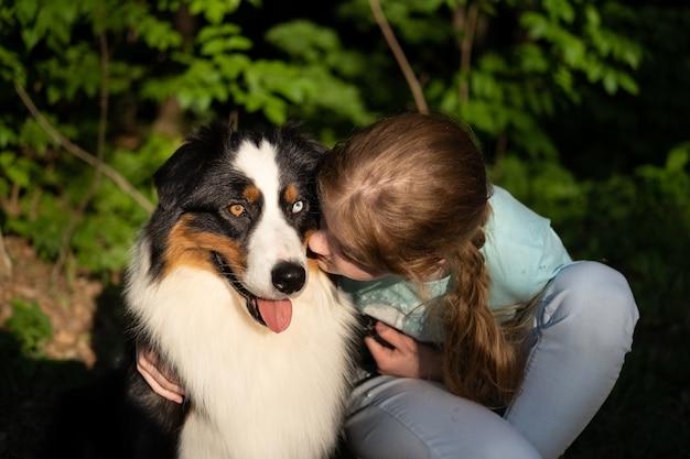 10대 소녀 포옹 키스 호주 양치기 개. 애완 동물 관리 개념입니다. 사랑과 우정