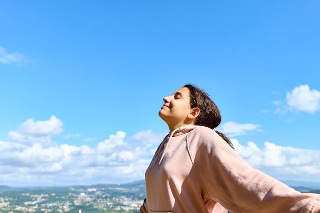 하루를 즐기고 심호흡을 하는 10대 소녀, 하늘이 배경입니다