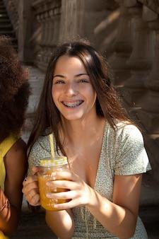彼女の飲み物を楽しんでいる10代の少女