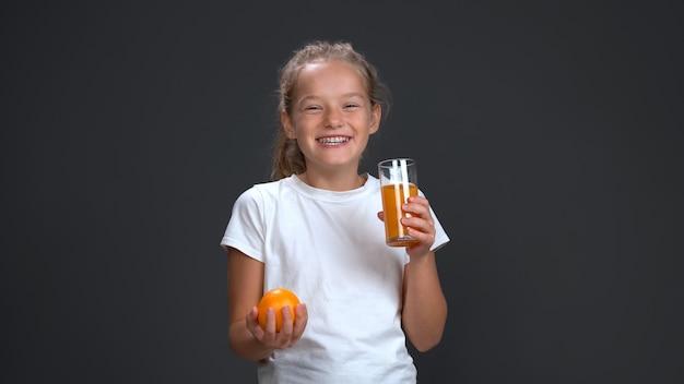 Девочка-подросток наслаждается стаканом апельсинового сока, держа в другой руке свежий апельсин. концепция здорового питания. изолированные на сером фоне. скопируйте пространство.