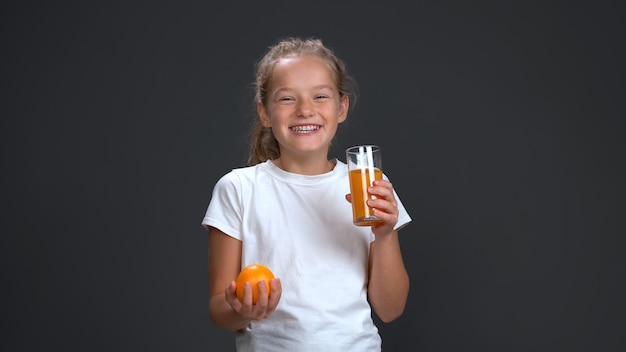 Teenage girl enjoys a glass of orange juice holding fresh orange in other hand. healthy food concept. isolated on gray background. copy space.