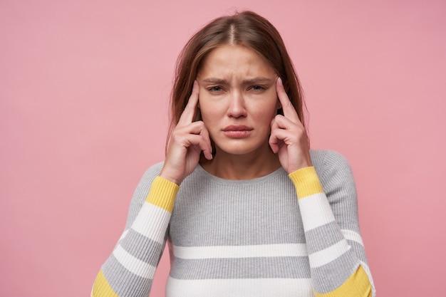 10代の少女、茶色の長い髪の痛みでヨーロッパの女性。ストライプのブラウスを着ています。彼女の頭をマッサージし、頭痛がします。パステルピンクの背景で隔離のカメラで見て