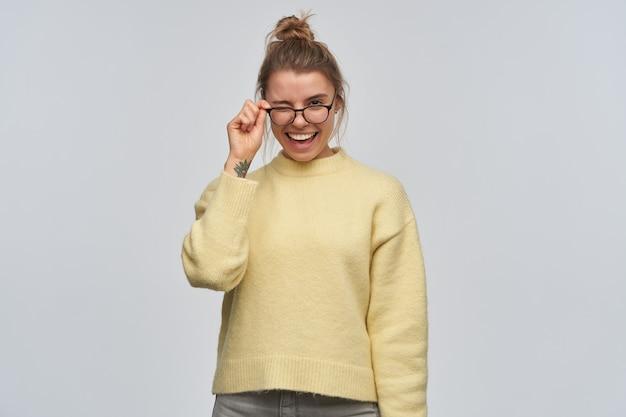 10代の少女、金髪の軽薄な女性がお団子に集まった。黄色いセーターとアイウェアを着ています。彼女の眼鏡に触れて見守ると、白い壁に隔離されたカメラにウィンクします