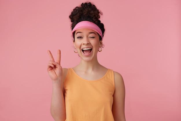 Teenage girl, flirty looking woman with dark curly hair bun. wearing pink visor, earrings and orange tank top. has make up. shows peace sing