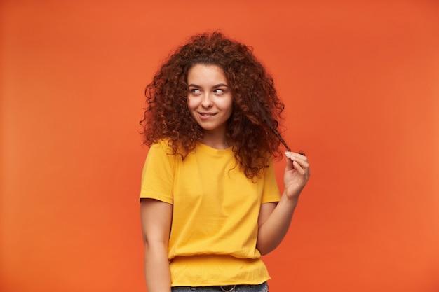 십 대 소녀, 노란색 티셔츠를 입고 생강 곱슬 머리를 가진 꼬리 치는 여자