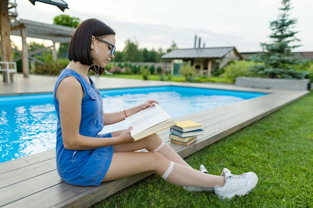 Teenage girl in glasses reads a book, background swimming pool