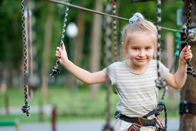 Teenage girl goes on hinged trail in rope park.