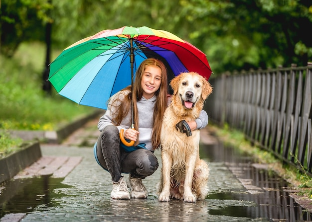 Teenage girl and golden retriever hiding from rain under colorful umbrella in city park