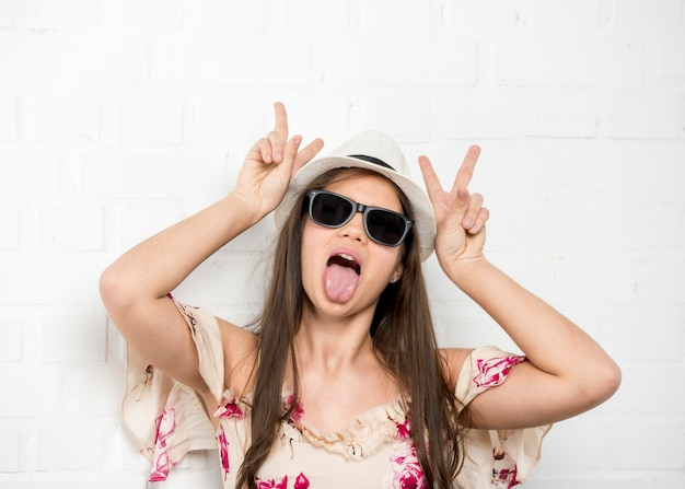 Teenage girl grimacing sticking out tongue and showing two fingers