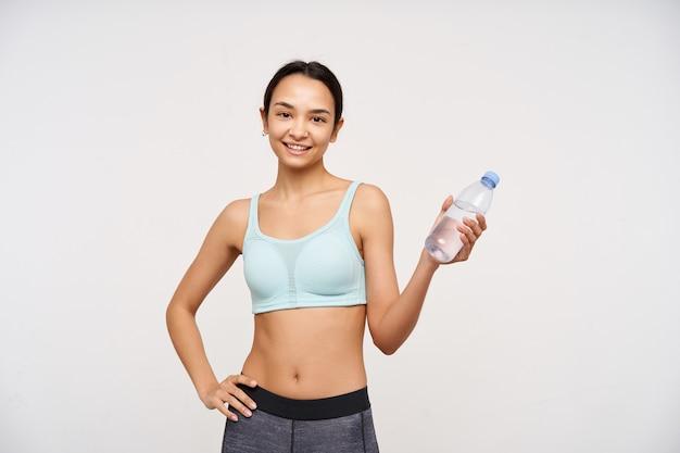 10代の少女、暗い長い髪の幸せそうなアジアの女性。スポーツウェアを着用し、ボトル入り飲料水を保持します。カメラを見て、白い背景の上に隔離され、腰に片手を保持します