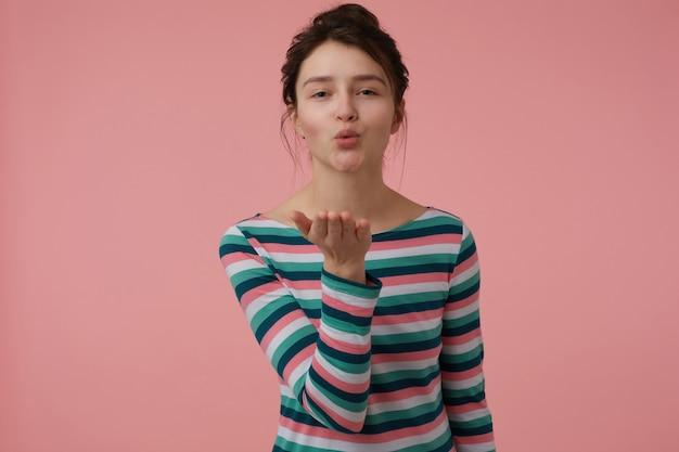 Девочка-подросток, счастливая, очаровательная женщина с волосами брюнетки и булочкой. носить полосатую блузку и послать поцелуй. эмоциональная концепция. изолированные на пастельно-розовой стене