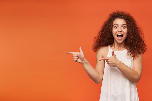 Teenage girl, happy looking, cheerful woman with curly ginger hair. wearing white off-shoulder blouse. pointing to the left at copy space, isolated over orange wall