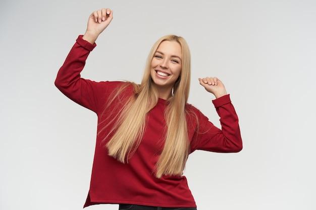 Девочка-подросток, счастливая смотря танцующая женщина с длинными светлыми волосами. в красном свитере. концепция людей и эмоций. смотрю в камеру, изолированные на белом фоне