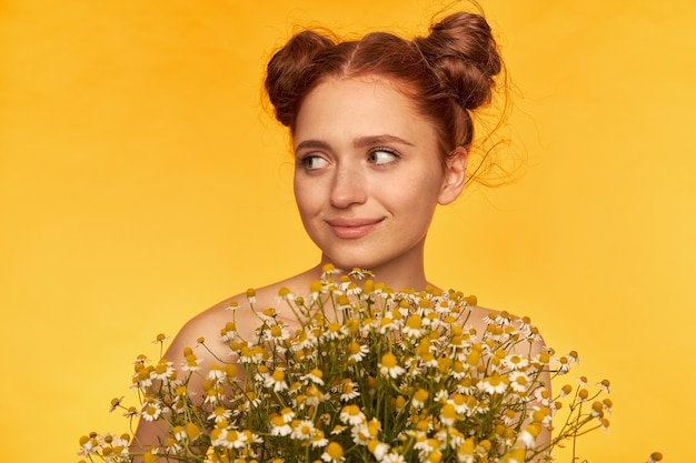 Teenage girl, happy looking red hair woman with two buns. hairstyle. holding a bouquet of wildflowers, smile and watching to the left at copy space over yellow wall. closeup