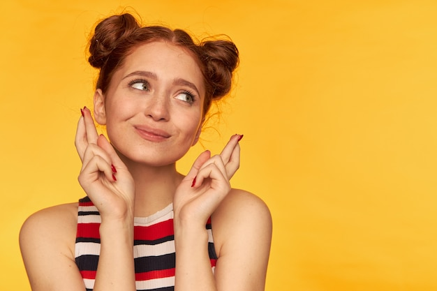 Adolescente, donna rossa sembrante felice dei capelli con due panini. indossare canottiera a righe e tenere le dita incrociate. concetto emotivo. guardando a destra nello spazio della copia sul muro giallo