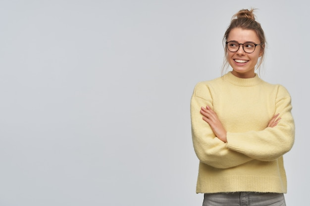 Teenage girl, happy looking woman with blond hair gathered in bun. wearing yellow sweater and glasses. keeps arms crossed on a chest. watching to the left at copy space, isolated over white wall
