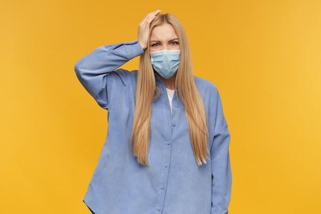 십 대 소녀, 금발의 긴 머리를 가진 행복 한 찾고 여자는 무서운 찡그린 얼굴로 머리에 그녀의 손을 유지합니다. 파란색 셔츠와 의료용 얼굴 마스크를 착용. 사람과 감정 개념.