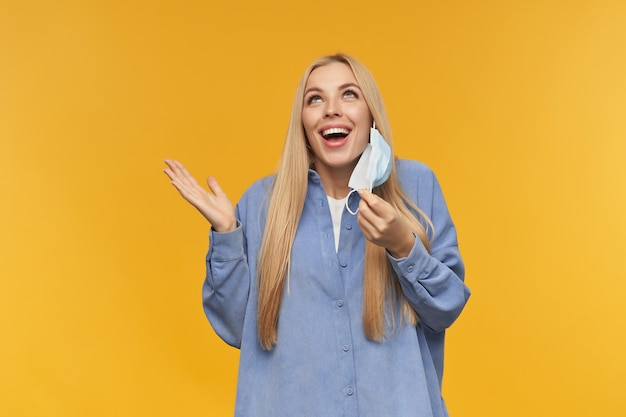 Ragazza adolescente, donna dall'aspetto felice con i capelli lunghi biondi. togliersi la maschera medica con un ampio sorriso. concetto di persone ed emozione. guardando in copia spazio, isolato su sfondo arancione