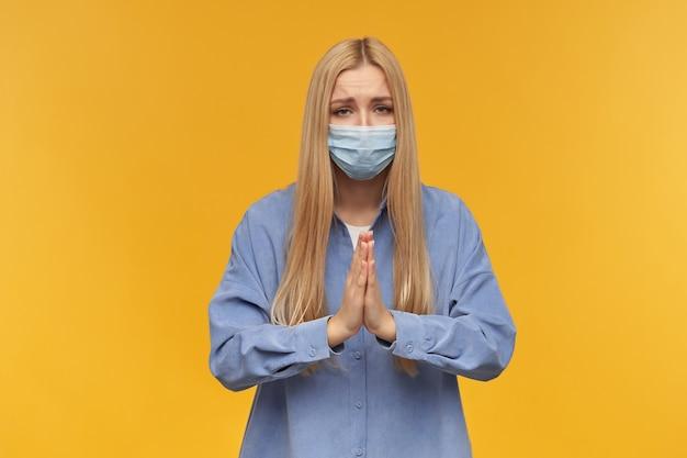 Ragazza adolescente, donna dall'aspetto felice con i capelli lunghi biondi. indossare maglietta blu e mascherina medica, pregando. concetto di persone ed emozione. guardando in alto, isolato su sfondo arancione