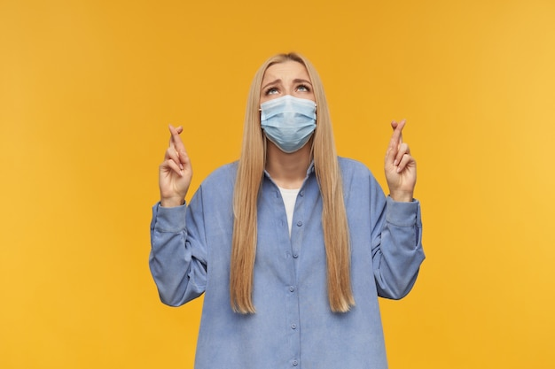 Teenage girl, happy looking woman with blond long hair. wearing blue shirt and medical face mask, praying with crossed fingers people and emotion concept. watching up, isolated over orange background