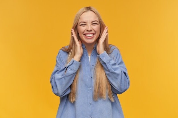 10代の少女、金髪の長い髪の幸せそうな女性。青いシャツを着ています。人と感情の概念。広く笑顔で興奮から目を細めます。オレンジ色の背景の上に分離されたカメラで見て