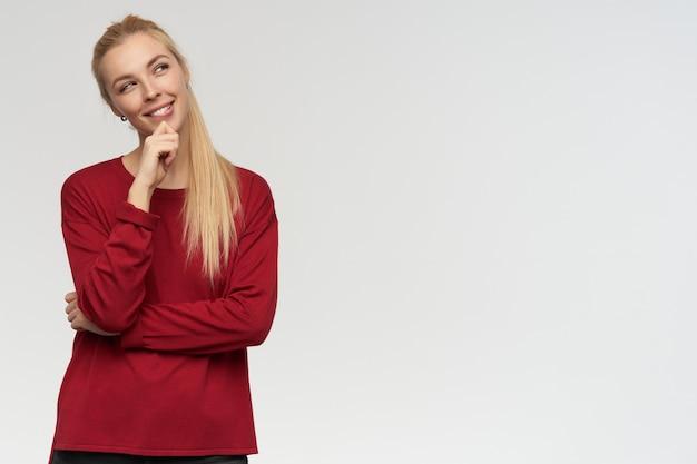 Ragazza adolescente, donna dall'aspetto felice con i capelli lunghi biondi. indossare un maglione rosso. concetto di persone ed emozione. guardando minuziosamente a destra in copia spazio, isolato su sfondo bianco
