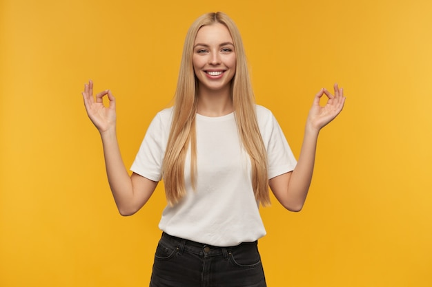 Девочка-подросток, счастливая женщина с длинными светлыми волосами. в белой футболке и джинсах. широко улыбается и показывает пальцами знак мудры, смотрит в камеру, изолированные на оранжевом фоне
