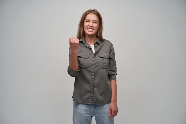 Adolescente, donna dall'aspetto felice con capelli lunghi castani. indossa una camicia grigia e jeans. concetto emotivo. tieni il pugno alzato e strizza gli occhi. guardando la telecamera isolata su sfondo grigio