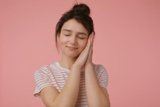 10代の少女、ブルネットの髪とパンを持つ幸せそうな女性。赤い帯のtシャツを着て、夢を見ながら寝ているふりをします。感情的な概念。パステルピンクの壁の上に隔離されたスタンド